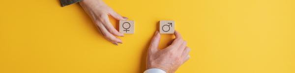 male and female hands holding male and female symbols